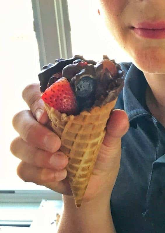 a boy holding a waffle cone filled with fruit.