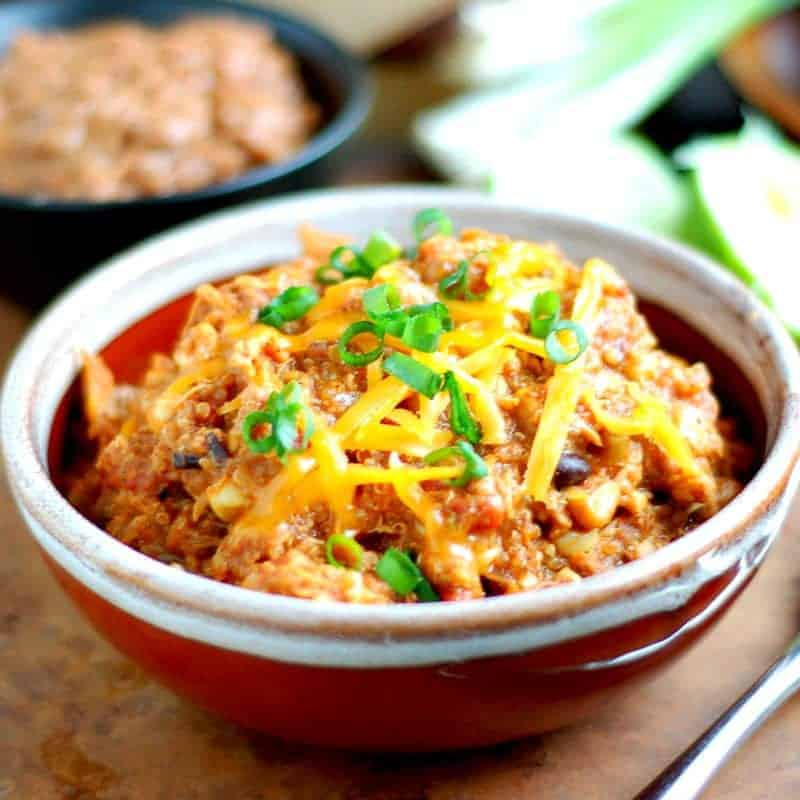 A brown bowl with creamy quinoa casserole with melted cheese and green onions on top.