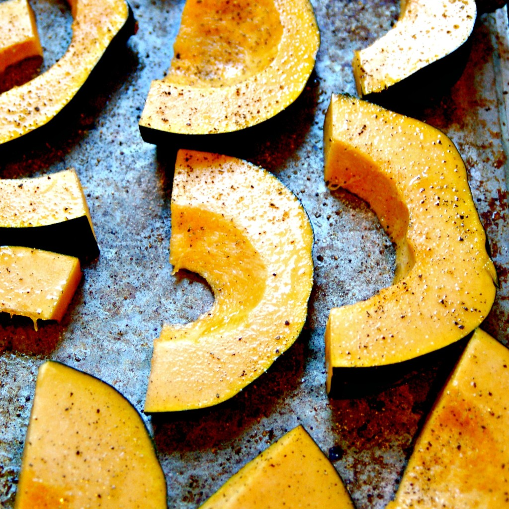 Sliced acorn squash shown on a baking pan seasoned with salt and pepper.