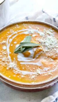 A bowl of butternut squash soup is shown on a white counter with coconut milk drizzled on top with a spoon and also fresh sage.
