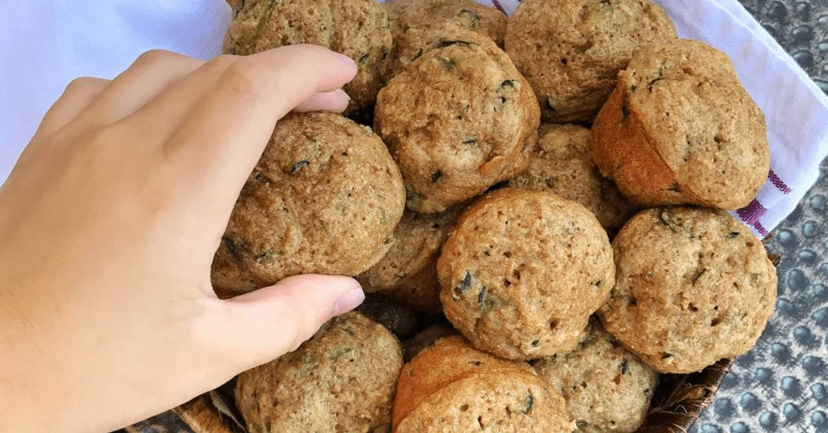 A child's hand is reaching into a basket of mini zucchini muffins.