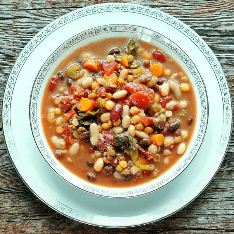 Slow cooker minestrone soup is shown after cooking in a white bowl with beans, carrots, spinach, and broth.
