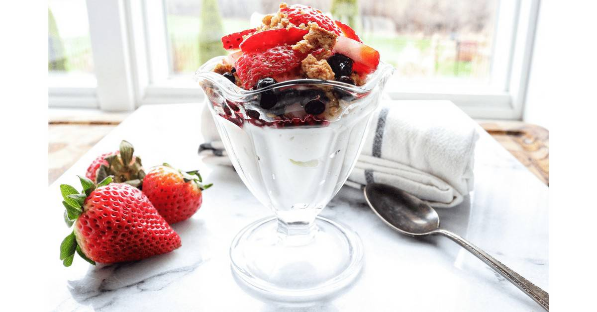 Yogurt parfait shown in a glass in front of a window with strawberries and a spoon next to it.