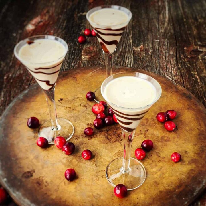 homemade Bailey Irish cream in tall stemmed glasses with chocolate drizzled in the glass.