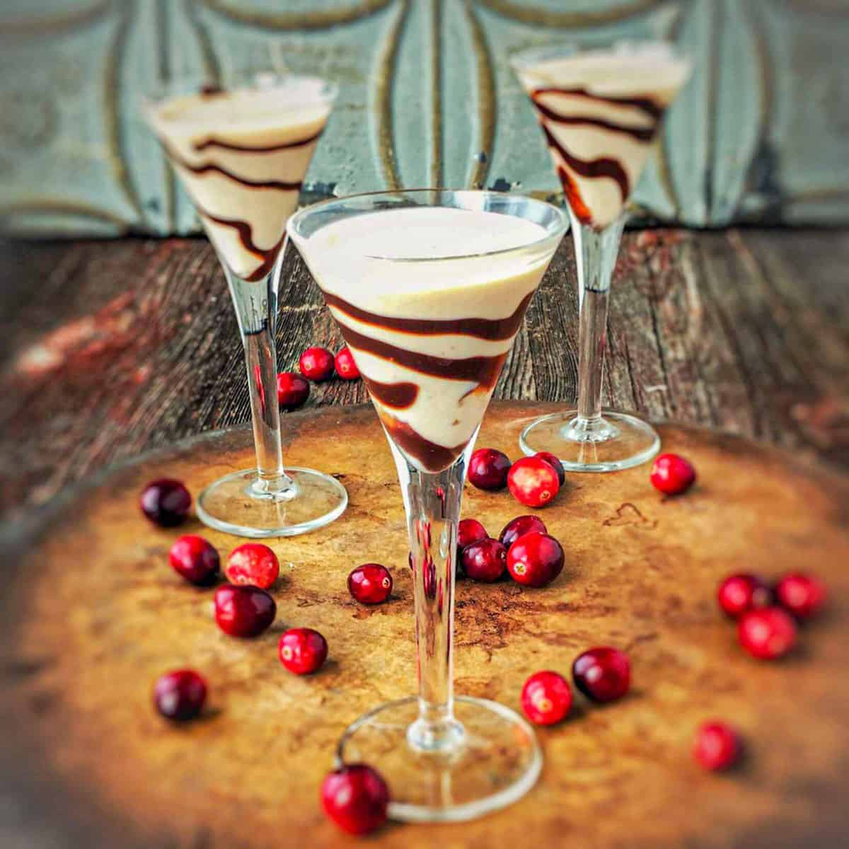 Homemade baileys shown in 3 stemmed glasses with chocolate swirled on the glass and cranberry on the wooden table below.
