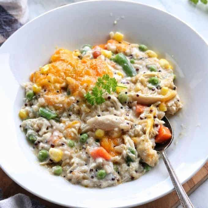 Turkey Casserole made with leftover turkey is in a white bowl including mixed veggies, rice, and cheese in a creamy sauce with a spoon in the bowl.