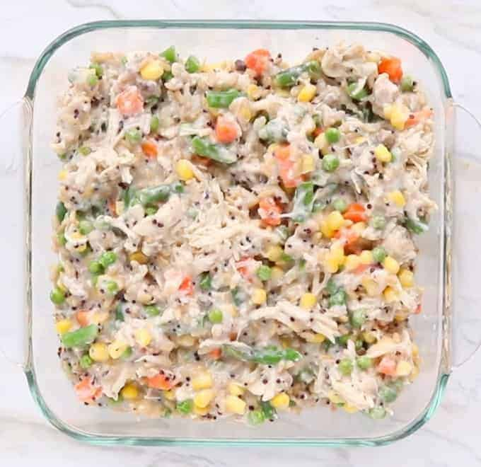Turkey Casserole with leftover turkey shown in a clear small baking pan with the casserole ready to be baked. You can see mixed veggies, turkey and rice in the creamy sauce.
