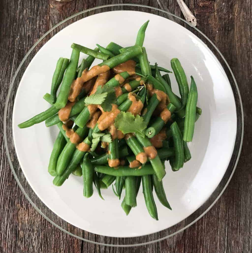 Veggie side dishes for dinner can be made quickly. This green bean satay with peanut butter cream sauce is simple and delicious. In just 10 minutes this beautiful vegetable side dish can be ready for the dinner table. Impress your guests and family at dinner tonight! via createkidsclub.com