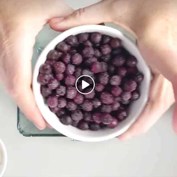 a small white bowl of frozen blueberries held in two hands above a blender on a white surface