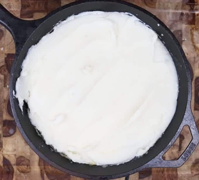Mashed potatoes are added on top of the crustless chicken pot pie in a black cast iron pan.