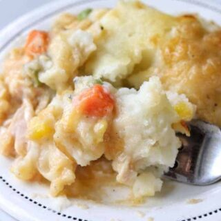 A close up of crustless pot pie showing mashed potatoes with mixed vegetables on a white plate with a fork.