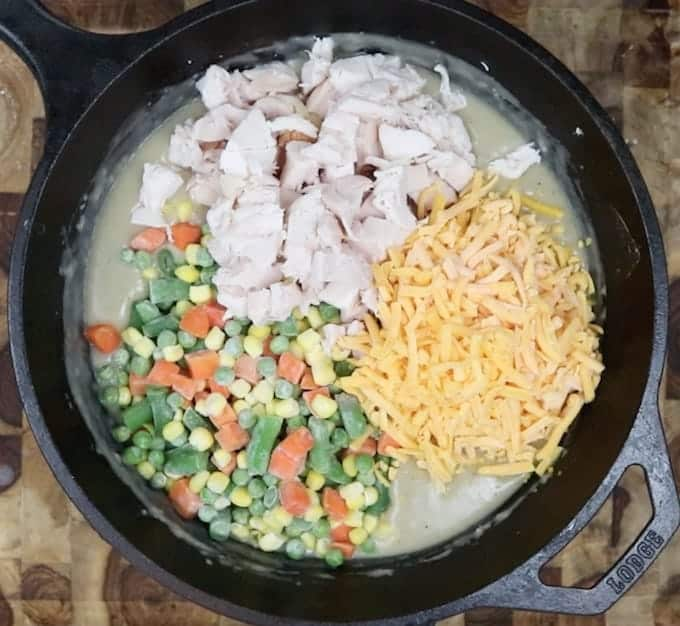 chicken, cheese, and veggie being added to the roux mixture in a black skillet.