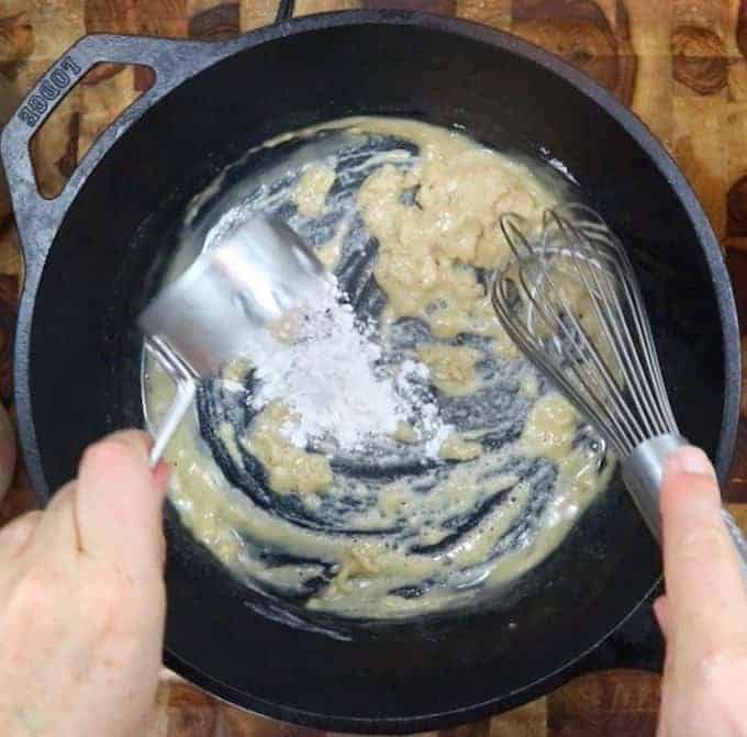 whisking butter and flour in a black skillet.