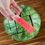 A half of a watermelon cut into watermelon sticks with one being held in front of the camera.