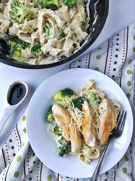 Fettuchini Alfredo in a white bowl with chicken tenders on top and broccoli.