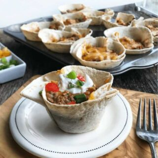 Baked Taco Cups are a healthy meal for kids and are simple to make. Made with beef, pork, or ground turkey these crunchy taco cups are a supper recipe hit! Crisp flour tortillas are loaded with veggies like diced tomotates. This healthy dinner idea even has refried beans blended in, but shh...no one will know! Top with your favorite taco toppers and dinner is ready! A 30 minute meal!