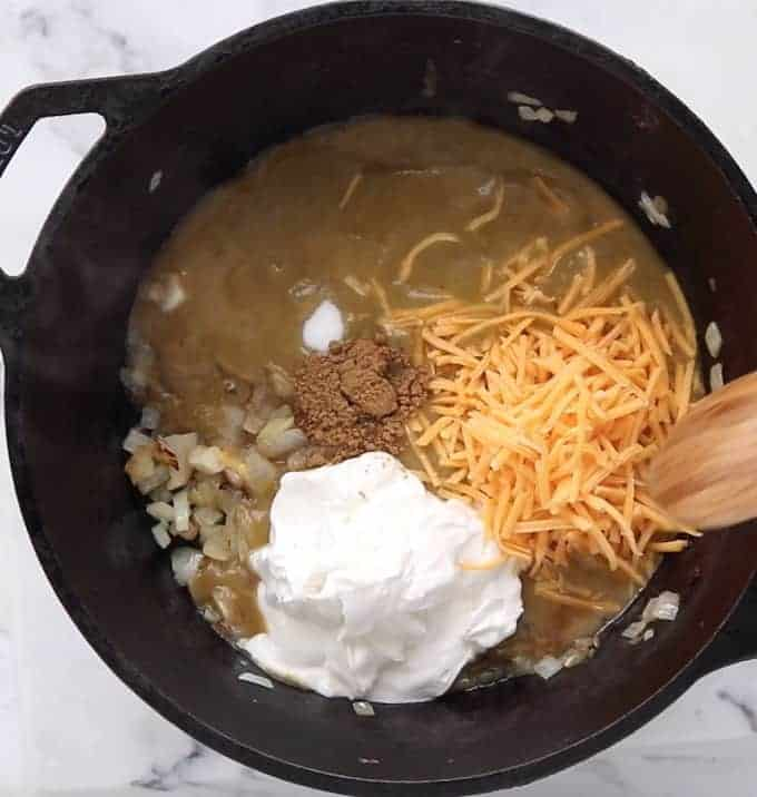 enchilada ingredients shown in a black skillet including cheese, greek yogurt, white beans, enchilada sauce and spices.
