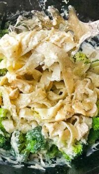 Chicken Alfredo with broccoli and wide noodles shown in a black cast iron skillet.