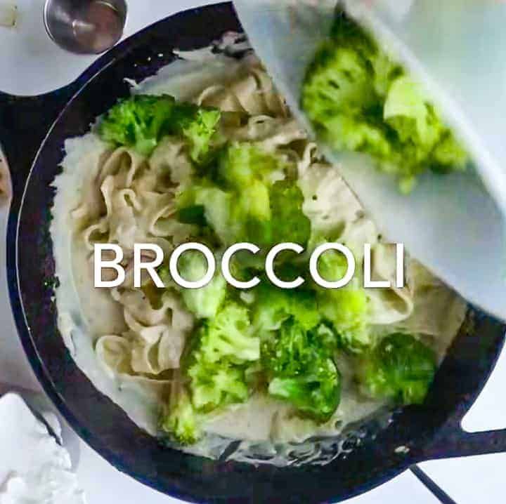 broccoli being added to the sauté pan with the Greek yogurt sauce, fettuccini noodles and chicken.