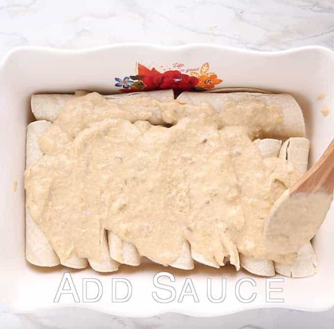 Chicken enchiladas shown rolled up in a white baking pan with the enchilada sauce on top.
