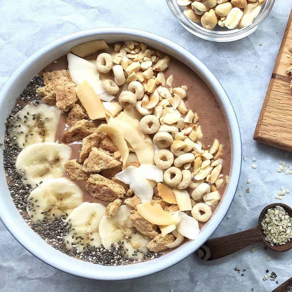 A close up of a peanut butter smoothie bowl with bananas, graham crackers and cheerios on top.