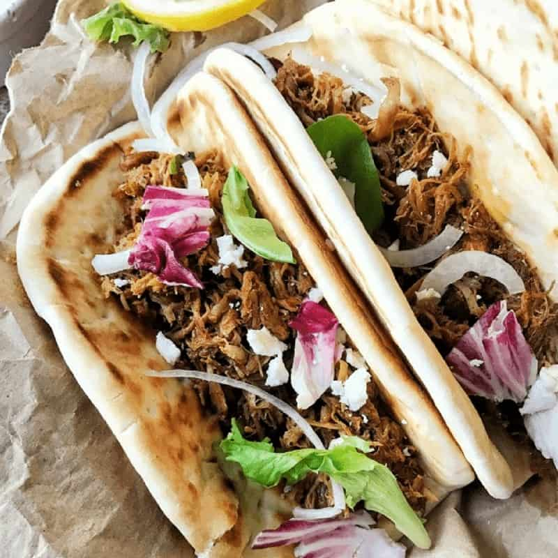 pulled pork is in a pita with lettuce, onions, and feta cheese.