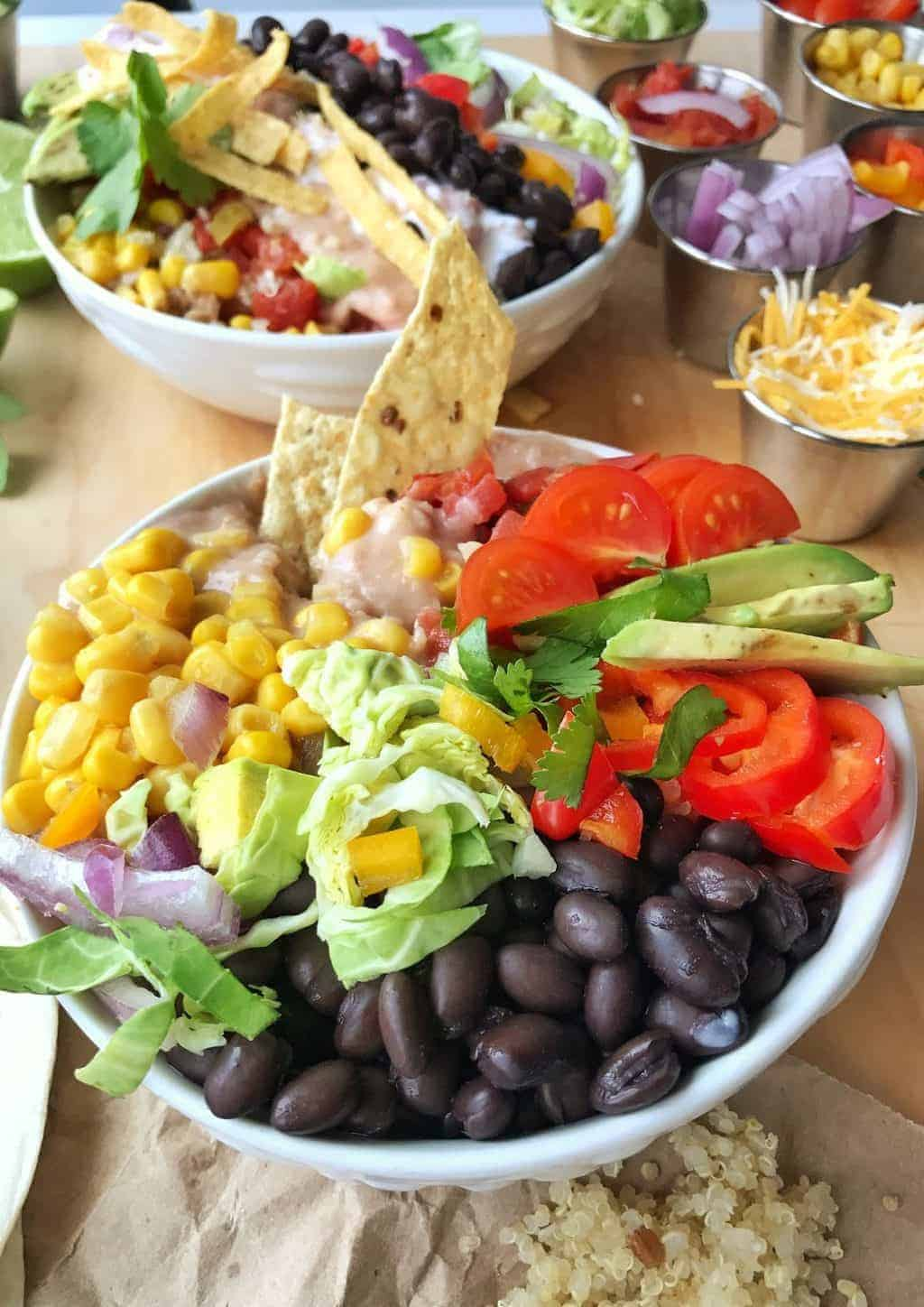 Nacho bowls with black beans, corn, tomatoes and avocado are shown in two white bowls with cheese and tortilla chips.