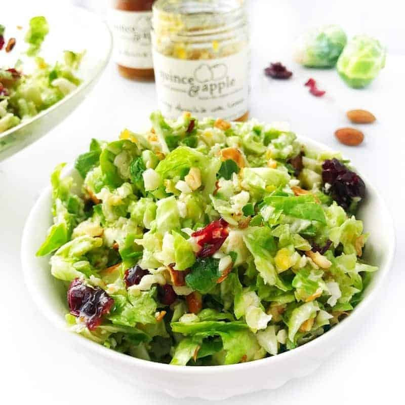 Shredded brussels sprout salad with almonds and dried cranberries shown in a white bowl.