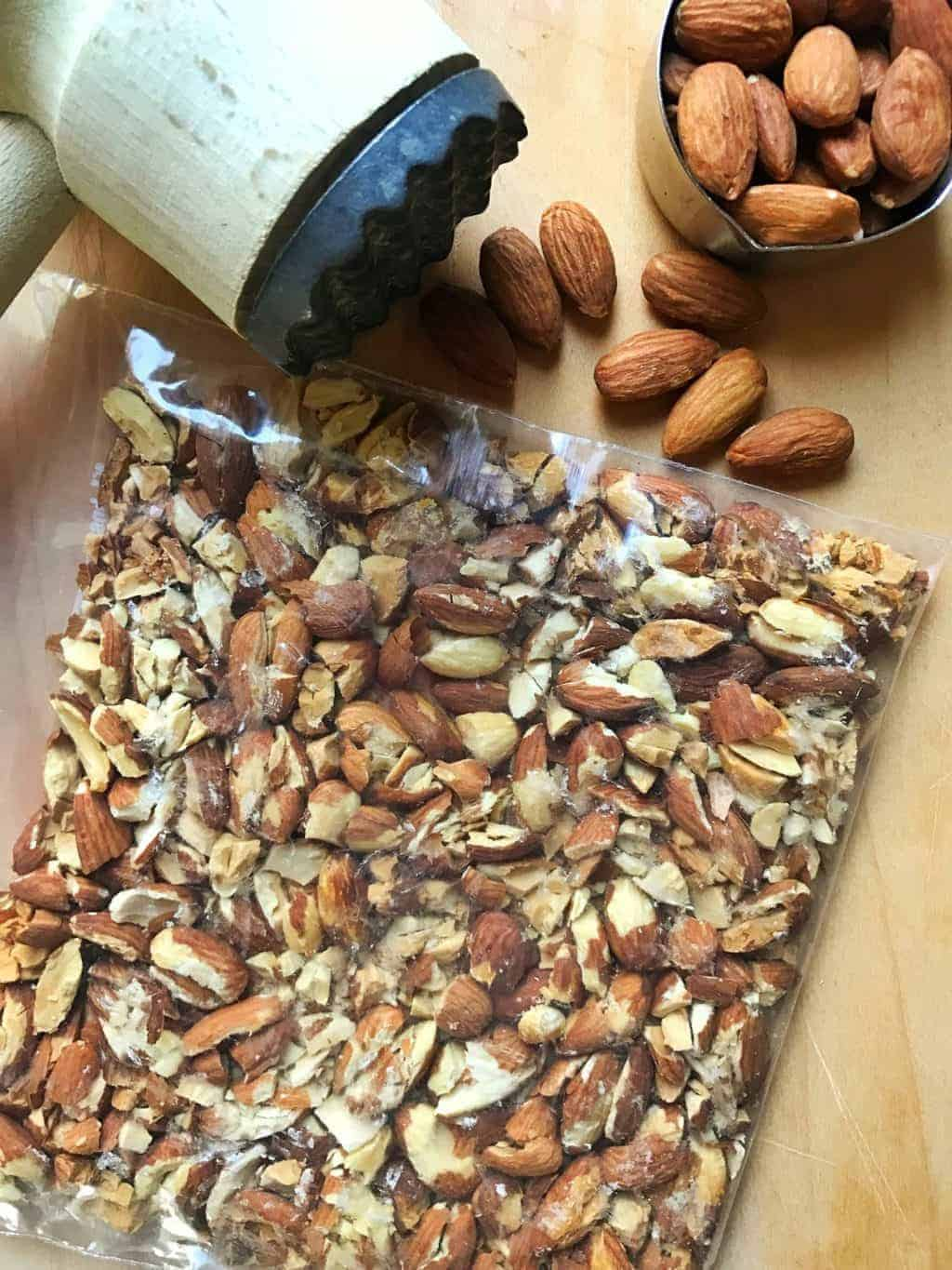 almonds shown in a ziplock bag on a cutting board with a mallet.
