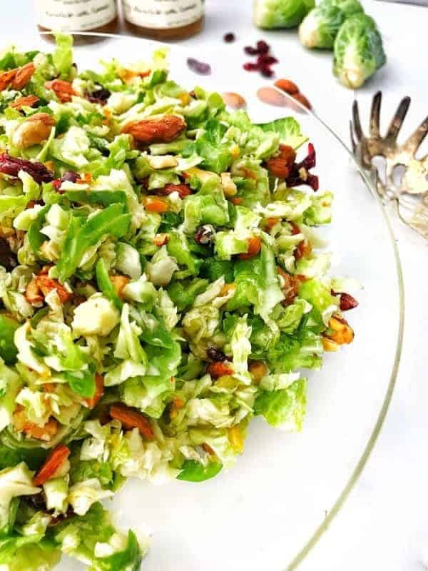 Shredded brussels sprout salad with almonds and dried cranberries shown in a clear bowl