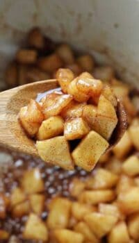 Sautéed diced apples caramelized in a baking pan with wooden spoon.