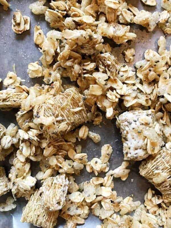a close up shot of baked granola on a baking sheet.