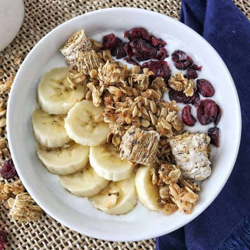 A white bowl has sliced bananas, nut free granola and dried cranberries with milk.