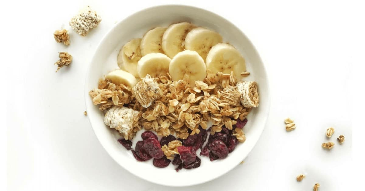 A white bowl has sliced bananas, nut free granola and dried cranberries with milk and a spoon.