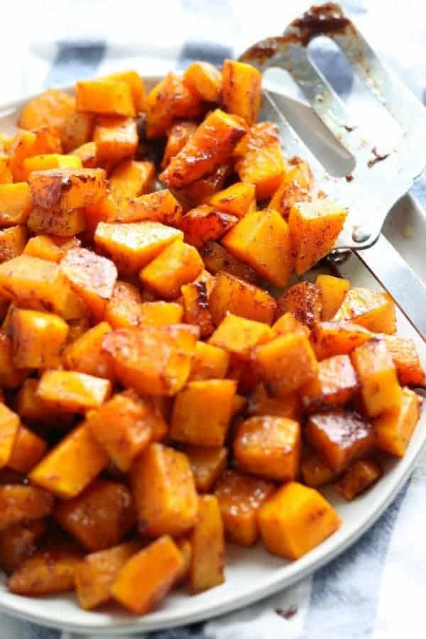 Roasted butternut squash recipes shown baked in cubes on a white plate with a metal spatula.