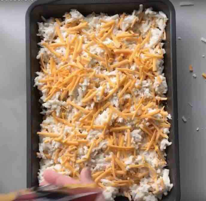 A 9x13 inch metal pan is filled with the cheesy potato mixture and topped with shredded cheddar cheese.