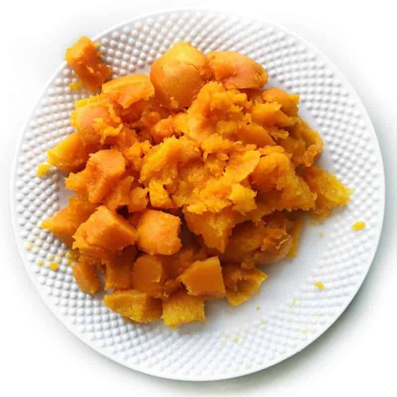 Slow Cooker Butternut Squash shown cooked on a white plate on a white background.