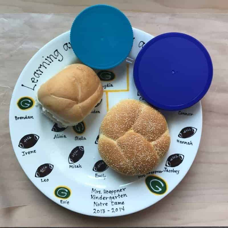 two hamburger buns next to peanut butter jar lids on a white plate that has footballs on it