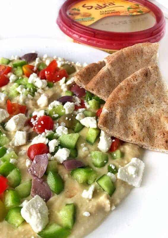 hummus dip on white plate topped with veggies and feta cheese with pita chips and a sabra hummus container in the background