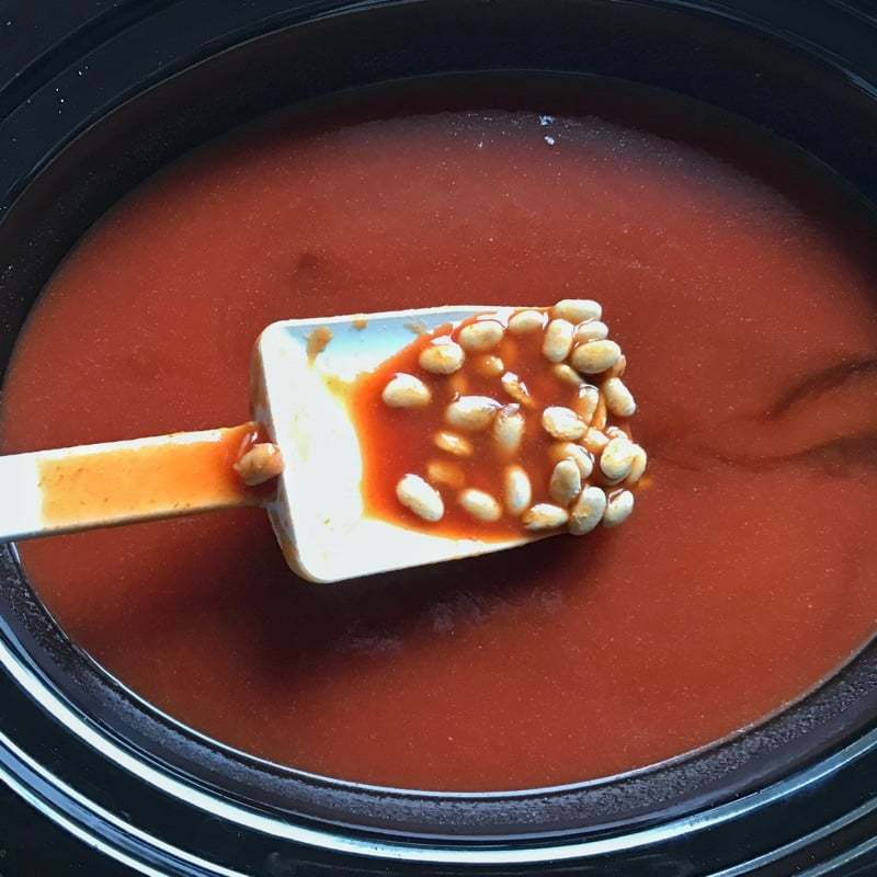 Pre-cooked baked beans in a black crockpot.