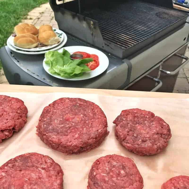 raw formed cheese stuffed burgers are on a tray by an out door grill.