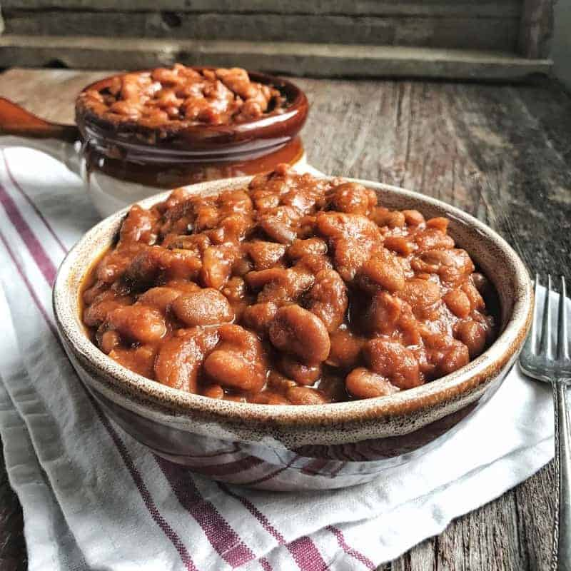 Crockpot baked beans shown in a brown bowl with a crock pot baked beans behind it all on a wooden surface.