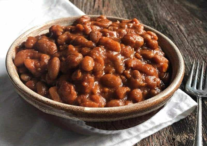 A bowl of crockpot baked beans on a wooden table with a white cloth underneath.