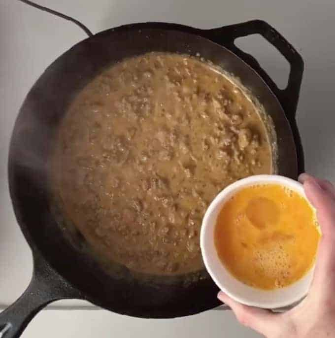 Butternut Squash Mac and Cheese being made in a cast iron pan, whisked eggs are being added to the ground meat mixture in the pan.