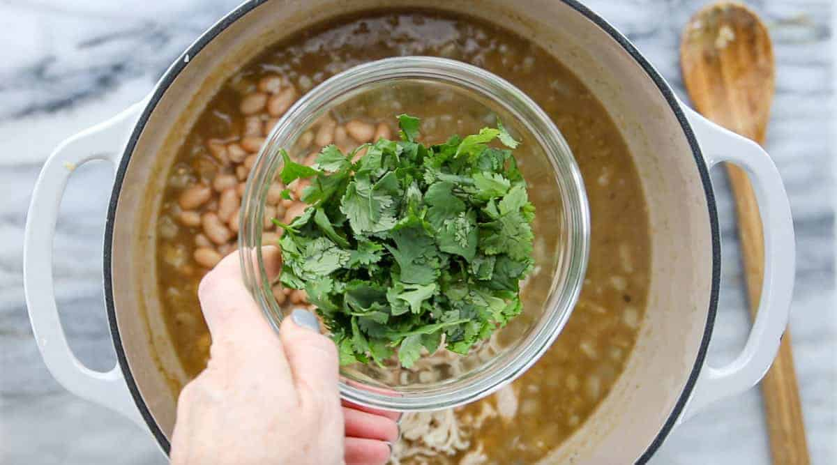 Chicken Tortilla Chip Casserole showing cilantro being added to the simmering stock pot