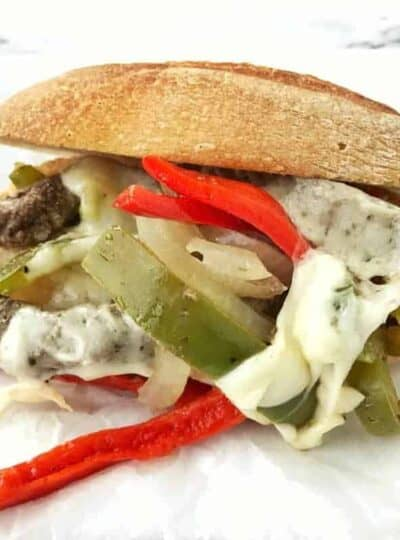 Philly cheese steak on a bun with green and red peppers.