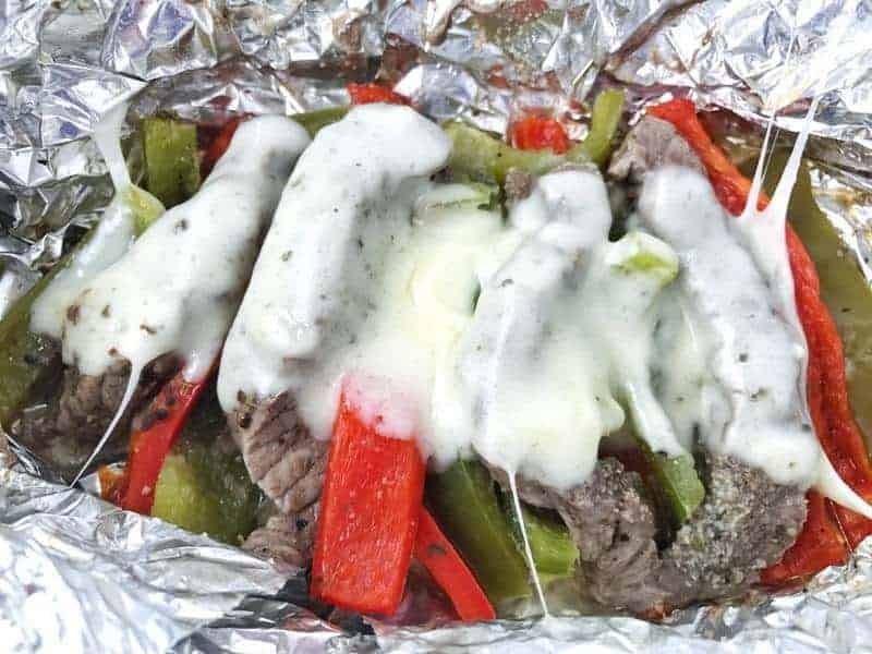 Strips of steak, red and green peppers with melted provolone cheese on top in a tin foil wrap