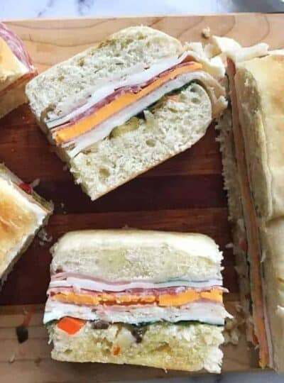 A sandwich cut in half on a plate, with Muffuletta
