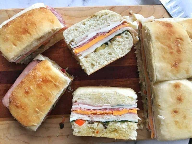 Muffuletta Sandwich shown sliced with cheese, meat, and olives showing.