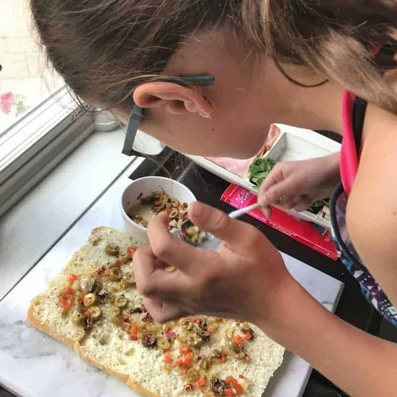 A small girl is spreading olive salad onto bread.